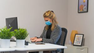 Woman with face mask working on her computer